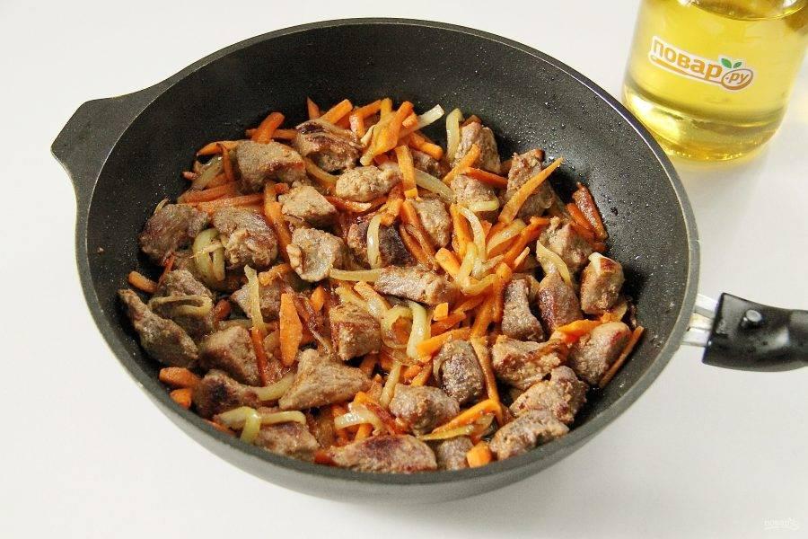 Затем добавьте нарезанную соломкой морковь и продолжайте обжаривать мясо с овощами еще 5-7 минут.