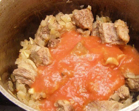 Бульон процедите через сито. А к луку и мясу добавьте перетертые помидоры.