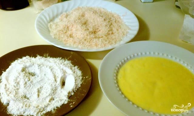 2. В отдельной миске взбиваем яйца и соль до однородности. В отдельную ёмкость высыпаем сухари, а еще в одну поместим муку. Каждую отбивную окунаем в яйцо, потом в муку и в сухарики.