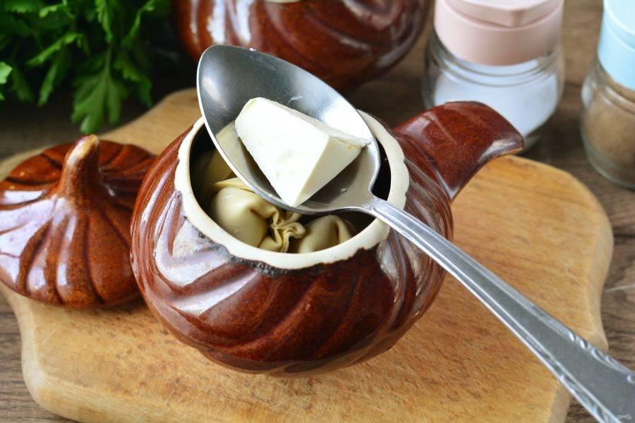 Залейте пельмени водой и добавьте в каждый горшочек по небольшому кусочку сливочного масла.