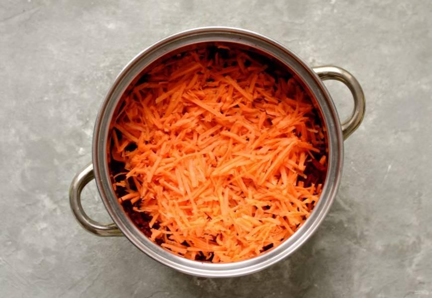 Морковь помойте, очистите от кожуры и натрите на крупной терке. Переложите в кастрюлю со свеклой.