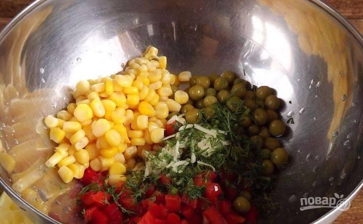 В большую миску выложите подготовленный сладкий перец. Откройте банку с кукурузой и горошком, слейте из них лишнюю жидкость. Добавьте ингредиенты в миску к сладкому перцу. Также выложите к ним чеснок и укроп, выдавите дольку лимона.