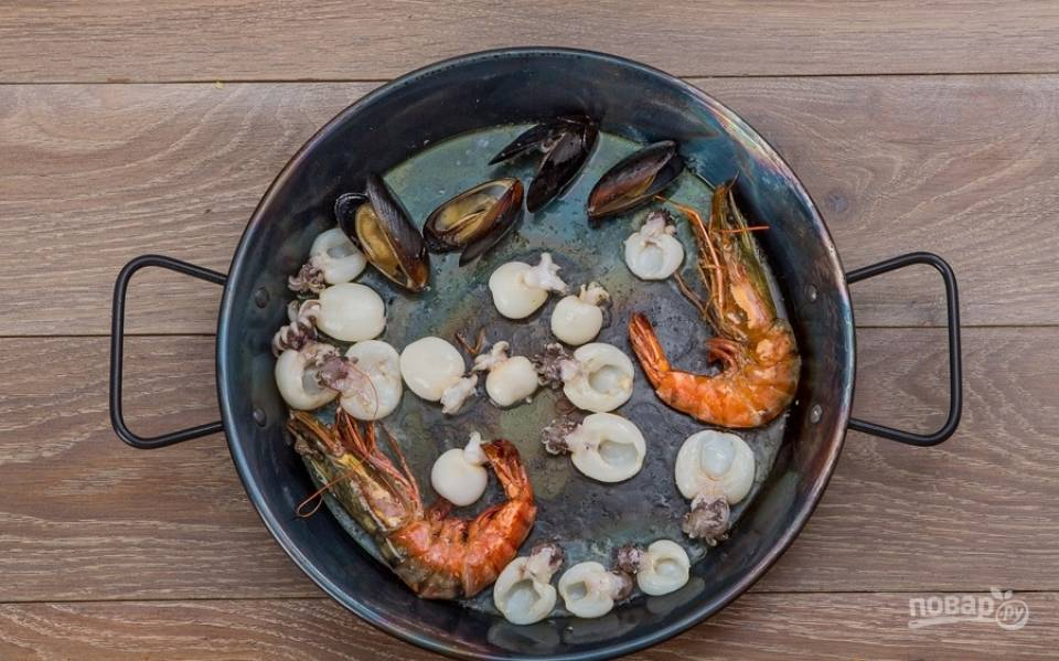 4. Специальную сковороду для приготовления паэльи отправляю на огонь, наливаю оливковое масло и выкладываю только что очищенные креветки, мидии и кальмары, обжариваю все не более 2-3 минут.