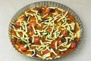 В форму выложить половинки помидоров черри и замаринованные цукини. Пиццу запекать при 180 °С около 20-30 минут.