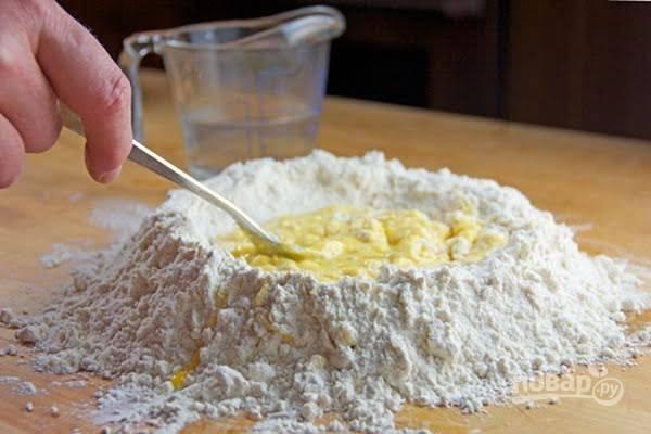 2. Начните аккуратно вмешивать яйцо в муку, а только после потихоньку подливайте холодную воду.