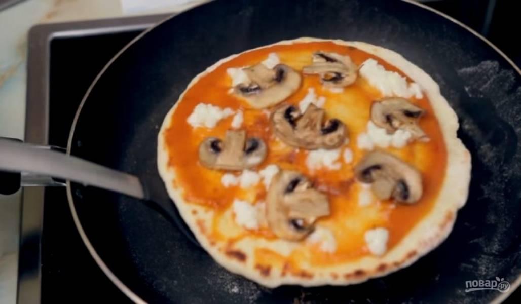 5. Тесто разделите на четыре части и раскатайте в лепешки. Обжарьте их на сухой сковороде с обеих сторон на среднем огне, поочередно смазывая их сливочным маслом.  Убавьте огонь и на обжаренную сторону нанесите соус. Выложите на пиццу начинку: натертую моцареллу и обжаренные шампиньоны