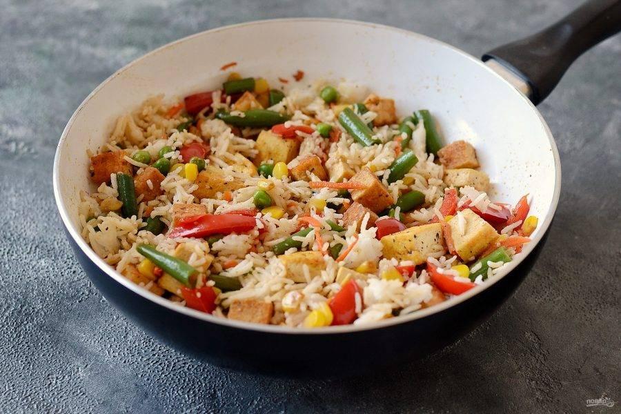 Затем добавьте вареный рис, аккуратно перемешайте и прогрейте 1-2 минуты все вместе.