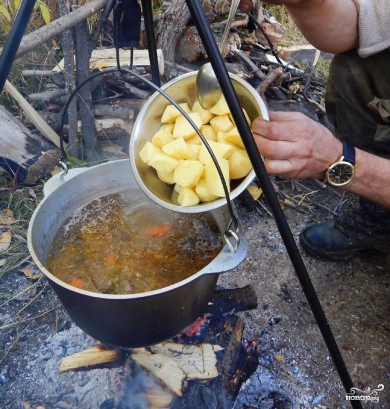 Следом в суп добавьте очищенный и крупно нарезанный картофель. Потом промойте и нарежьте яблоки, помидоры, перцы. Закиньте продукты в бульон. Добавьте очищенный чеснок и разрезанный пополам чили.