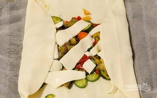 2.Раскатайте в пласт слоеное тесто, выложите овощи, сверху разместите ломтики сыра (можно натереть сыр на терке), сверните в рулет, хорошо закрепив все края.