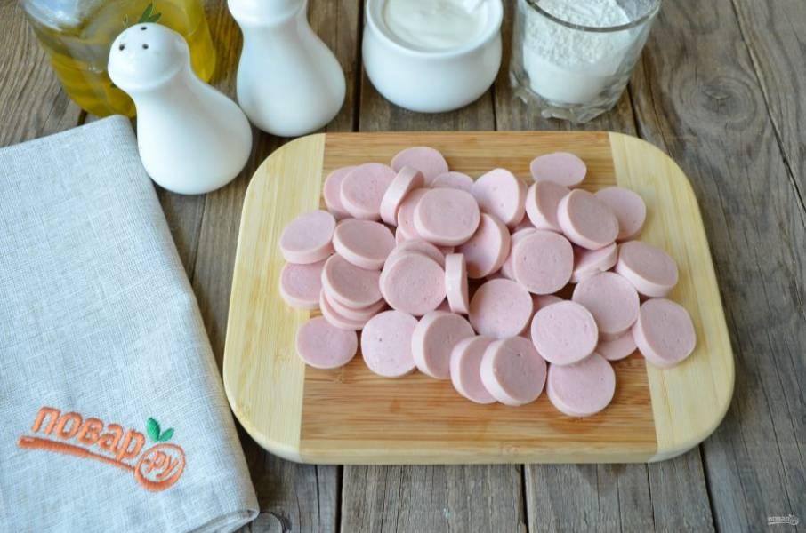 Пока варится капуста, порежьте сосиски кружочками.
