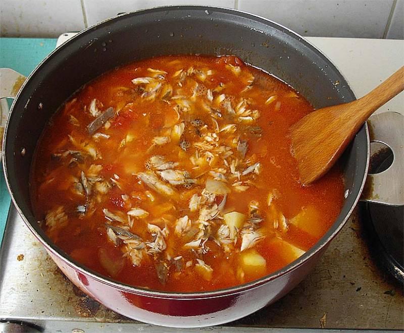Теперь добавляем в рыбный бульон тушеные овощи, кусочки рыбы и порезанный на мелкие кубики картофель. Варим на медленном огне 30 минут.