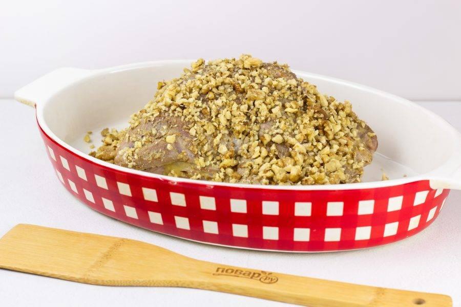 Орехи немного пробейте блендером, но не в крошку, высыпьте в большую миску. Обваляйте мясо со всех сторон в орехах и выложите в форму для запекания.