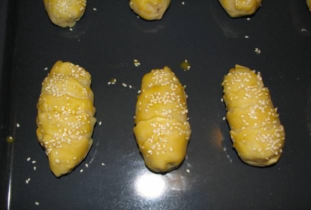 9. Сверху самсу смажьте взбитым яйцом и присыпьте кунжутом. Выложите на противень, застеленный пергаментом или смазанный маслом. Отправьте в разогретую духовку.