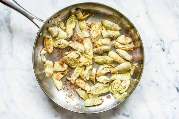 2. Тем временем отварите любые макароны по вашему вкусу и дайте им остыть. Пока они остывают, на раскаленную сковороду с маслом отправьте нарезанные пополам артишоки и жарьте их до золотистого цвета.