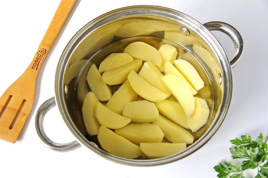 Картофель очистите, нарежьте дольками, поместите в кастрюльку и залейте водой. Отварите в течение 5 минут после закипания.