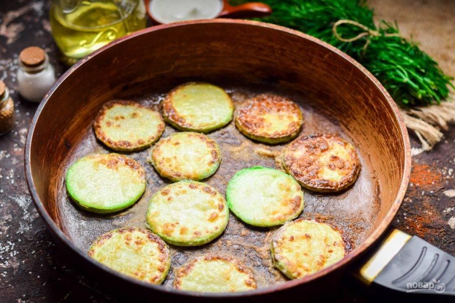 После поджарьте кружочки кабачка на сковороде,  в нескольких ложках растительного масла.