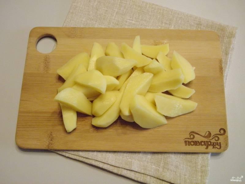 Очистите картофель, порежьте его на 4 части.