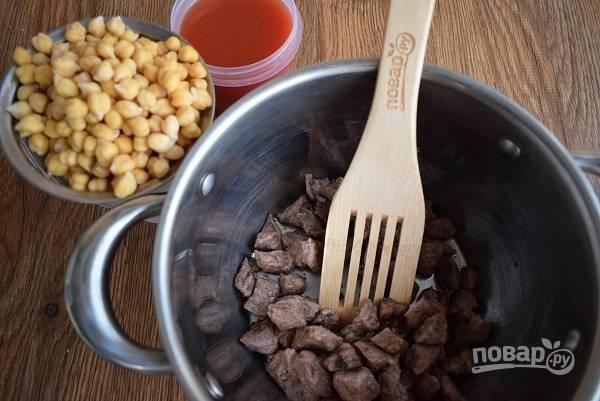 Масло разогрейте в казане или сковороде с высокими бортами. Мясо нарежьте на мелкие кубики и обжарьте с двух сторон до румяной корочки.