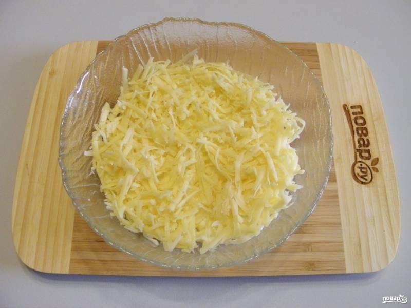 Второй слой салата - тертый сыр. Распределите его равномерно.