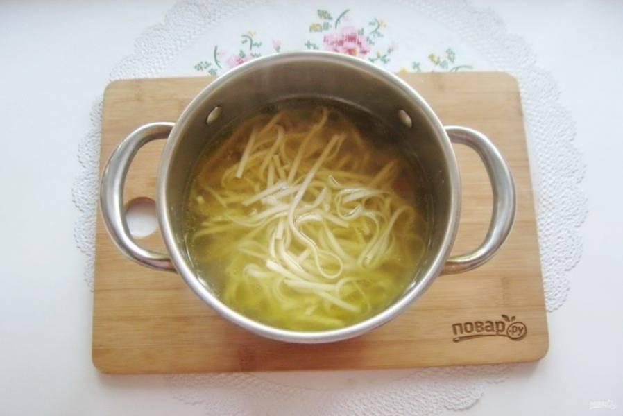 Выложите отварную лапшу в кастрюлю с супом.