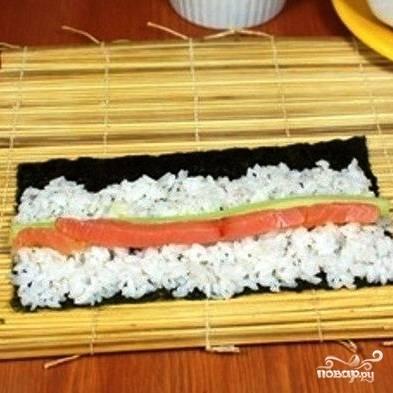 На бамбуковый коврик выкладываем лист нори, по которому равномерно тонким слоем распределяем рис. Прямо в середину риса выкладываем начинку - тонкие кусочки лосося, огурца и авокадо.
