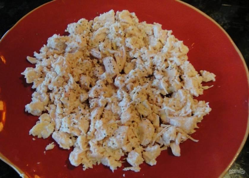 1.Нарежьте отварную курицу кусочками и уложите нижним слоем, поперчите и посолите.
