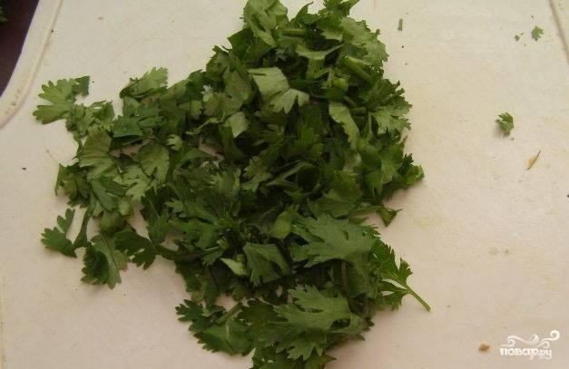 4. Подготовьте для салата кинзу. Для этого возьмите пучок зелени. Пересмотрите ее, чтобы не попадались желтые листики. Тщательно промойте и оставьте, чтобы стекла лишняя влага. Затем нарежьте.