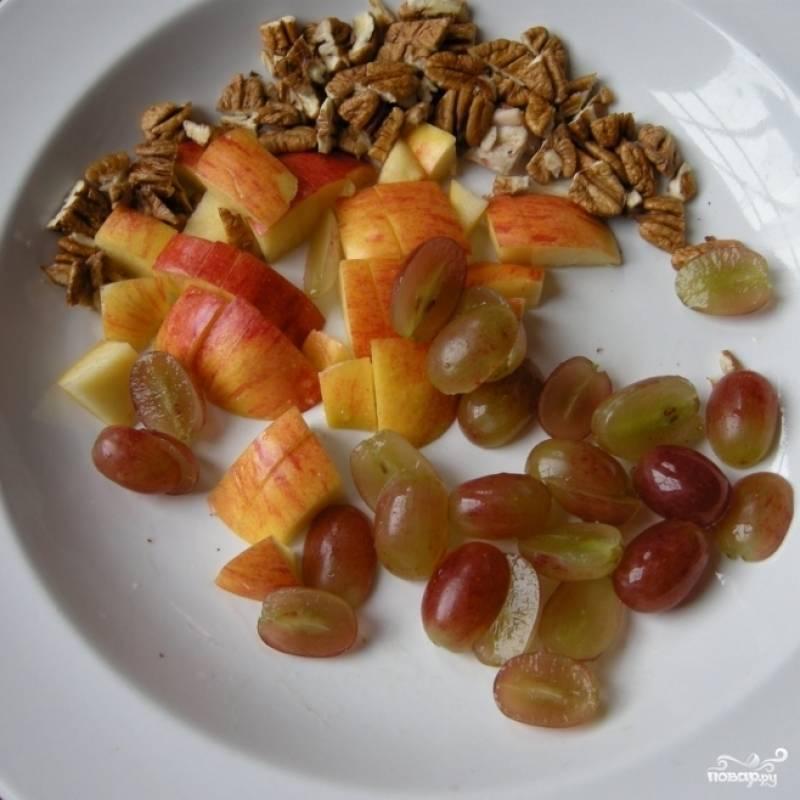 Виноград без косточек разрезаем на половинки, орехи измельчаем, яблоко нарезаем на небольшие кубики.