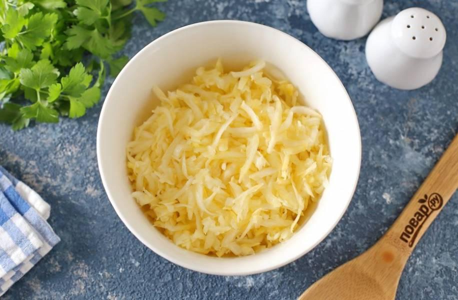 Кабачок натрите на крупной терке, добавьте щепотку соли, перемешайте и оставьте на 10 минут. Затем хорошо отожмите от выделившегося сока и переложите в глубокую миску.