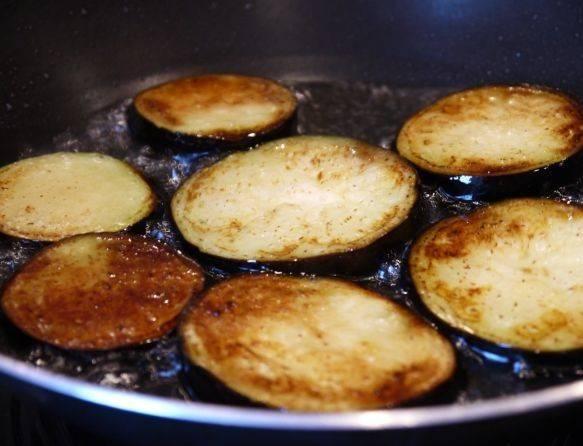 3. Теперь приступаем к баклажанам: почистите овощ, нарежьте кольцами и обжарьте на растительном масле с двух сторон.