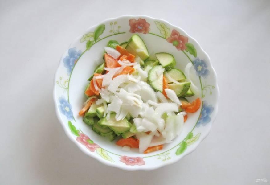 Репчатый лук очистите, помойте и нарежьте. Выложите в миску к моркови и кабачкам.