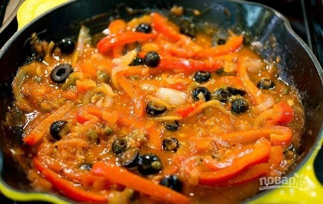Потом добавьте измельчённый чеснок, маслины половинками, томатный соус, вино, орегано и острый перец. Ингредиенты перемешайте.