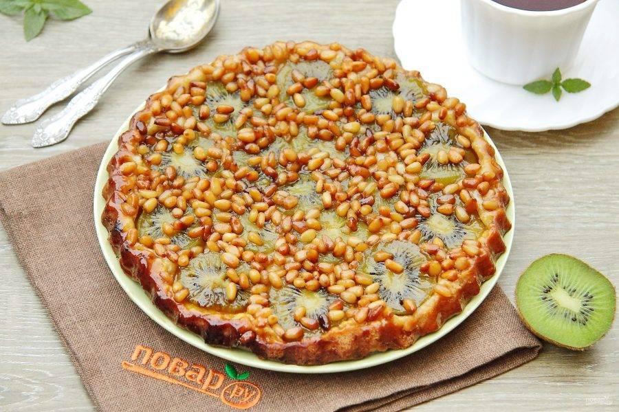 Выпекайте при 200 градусах 20 минут. Дайте выпечке немного остыть, после чего переверните на плоское блюдо начинкой вверх. Пирог-перевертыш с киви и кедровыми орешками готов.