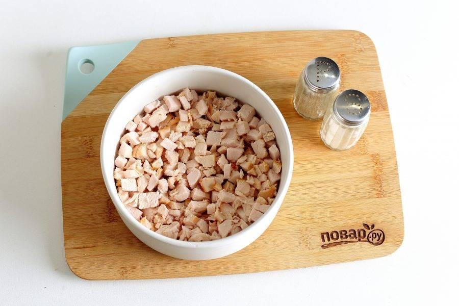 Куриное филе нарежьте мелкими кубиками и выложите первым слоем. Смажьте грудку майонезом.