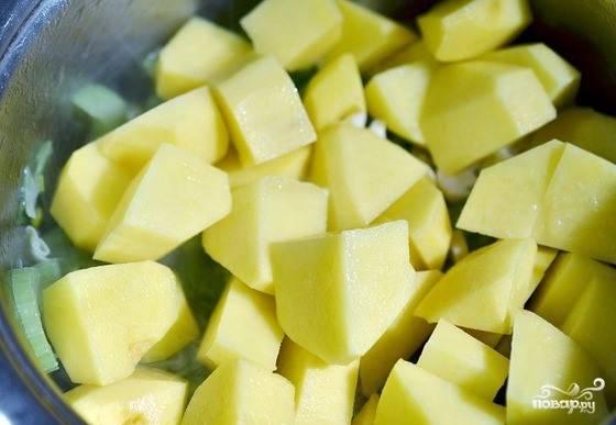 Картофель очистите и промойте. Затем нарежьте клубни на небольшие кубики. Отправьте картошку к луку и сельдерею. Обжаривайте ее, пока не появится легкая золотистая корочка.