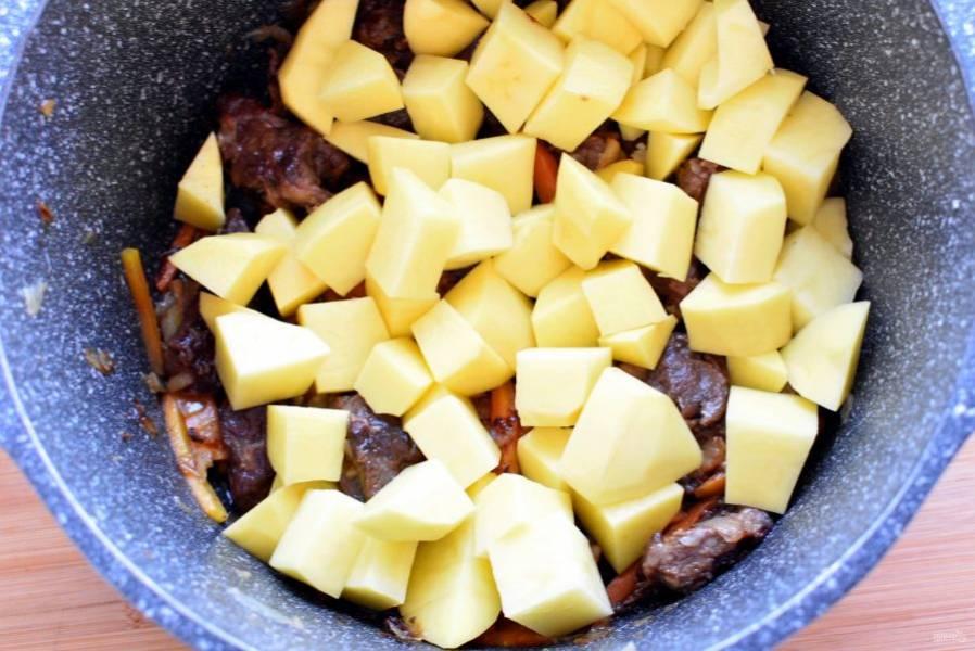 Добавьте  картофель, нарезанный крупными кубиками. Обжарьте до легкой корочки.