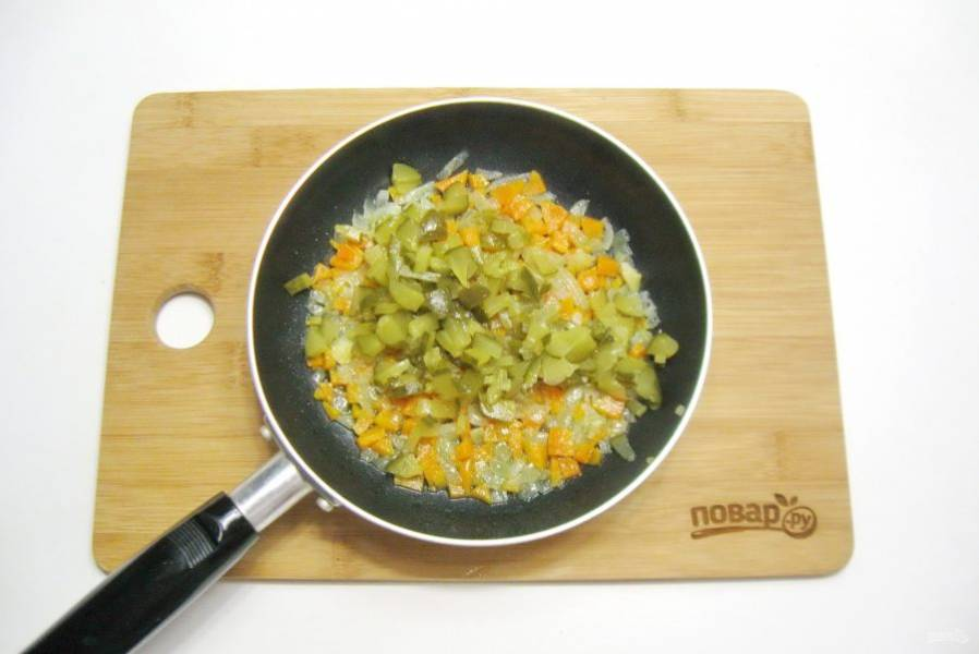 Добавьте нарезанный маринованный огурец. Тушите овощи еще 10 минут.