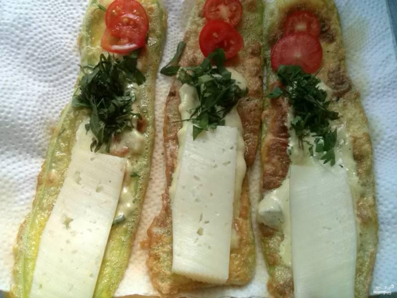"""Выкладывайте обжаренные """"язычки"""" на бумажную салфетку для того, чтобы стекло лишнее масло. Смажьте каждый сметаной с чесноком. С одного края — 1-2 ломтика помидора, с другого — ломтик сыра, посыпьте зеленью."""