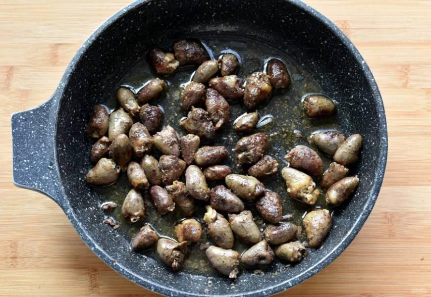Куриные сердечки промойте, очистите от лишнего жира и сосудов и обжарьте на ложке масла в сковороде до румяной корочки и почти полной готовности.