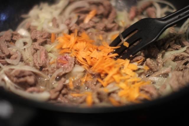 3. К мясу отправляем лук (нарезанный полукольцами) и нашинкованную на терке морковь.