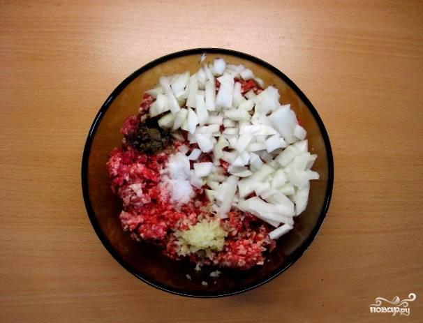 Теперь выложим фарш в другую миску. Вторую луковицу нарубим мелко. Потрем чеснок на терке. Добавим соль и перец. Перемешаем.