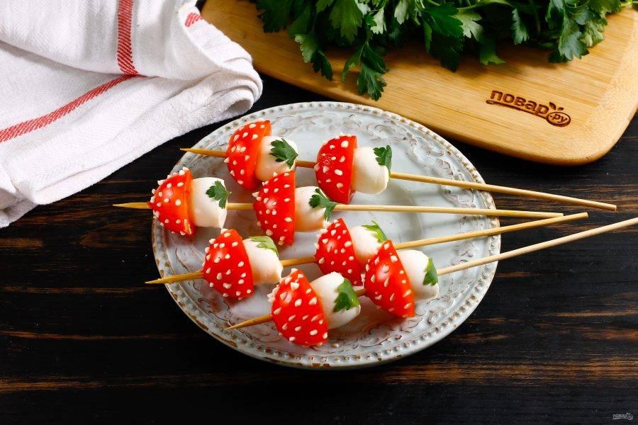На основание моцареллы приклейте по небольшому листику петрушки с помощью воды, верх грибочков украсьте капельками майонеза любой жирности.