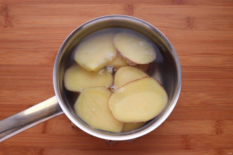 Картофель нарежьте пластинками толщиной в 0,5 см и отварите в подсоленной воде почти до готовности.