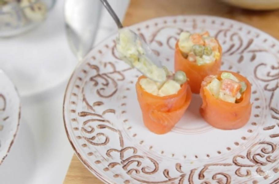 3. Семгу нарежьте на тонкие полосочки и сверните из них рулеты так, чтобы внутрь можно было выложить начинку. В рулетики из семги выложите салат с помощью ложки. Украсьте зеленью. Приятного аппетита!