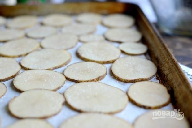 2. Выложите картофель на противень, устеленный пергаментной бумагой. Посыпьте картошку солью и перцем.