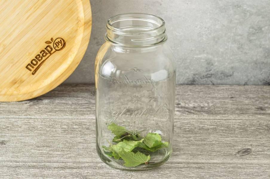 На дно чистой стерилизованной банки выложите лавровый лист, листья смородины и гвоздику.