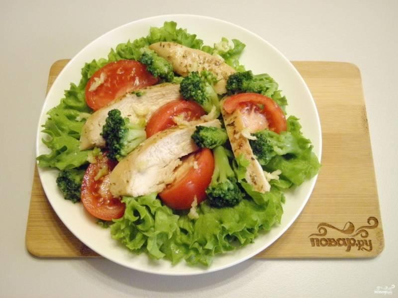 Разложите на листьях жаренное мясо (порезанное длинными кусочками), помидоры и брокколи. Раздавите чеснок через пресс и распределите по салату. Посолите, приправьте травами.