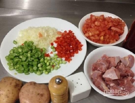 Подготовим продукты. Мясо кролика тщательно промоем и нарежем на небольшие кусочки. Маленькими кубиками нарежем лук, болгарский перец и помидоры. Спаржевую фасоль тоже нарежем на небольшие кусочки.