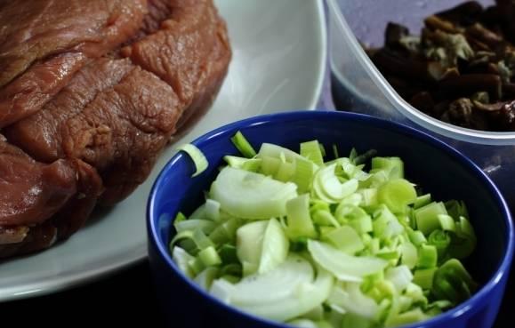 Для начала подготовим все необходимые ингредиенты: мясо промоем и высушим при помощи бумажных салфеток, натрем телятину солью и перцем, желтый лук и лук-порей нарежем полукольцами, а грибы отвариваем до полной готовности и смешиваем с солью и молотым перцем.
