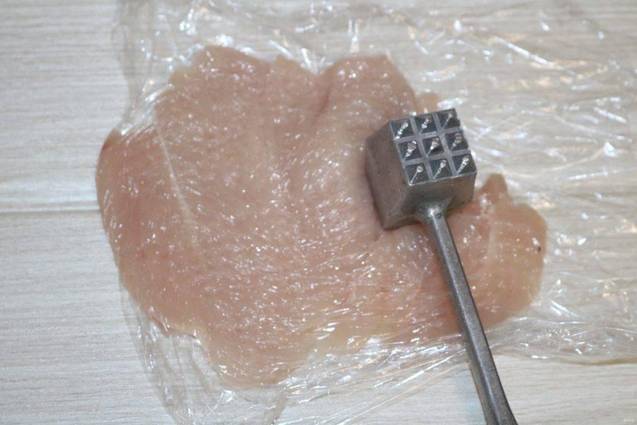 Разложите куриную грудку на пищевой плёнке, отбейте её с двух сторон.